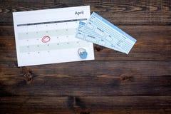 计划一次旅行 买飞机票 在日历附近的票与日期在黑暗的木背景顶视图拷贝空间盘旋了 免版税图库摄影