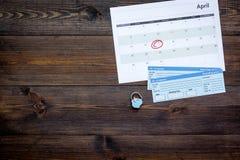 计划一次旅行 买飞机票 在日历附近的票与日期在黑暗的木背景顶视图拷贝空间盘旋了 图库摄影