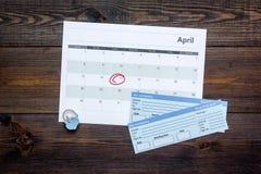 计划一次旅行 买飞机票 在日历附近的票与日期在黑暗的木背景顶视图拷贝空间盘旋了 免版税库存图片