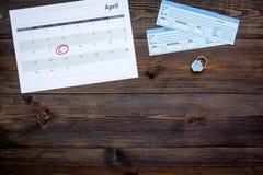 计划一次旅行 买飞机票 在日历附近的票与日期在黑暗的木背景顶视图拷贝空间盘旋了 库存图片