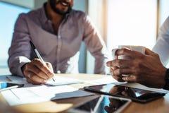 计划事务的企业投资者坐在桌上在办公室 免版税图库摄影