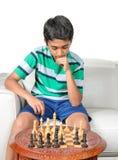 计划他的接下来的步骤的年轻男孩在一盘棋期间 库存图片