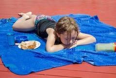 计划在阳光下在一条蓝色毯子的女孩 免版税库存照片