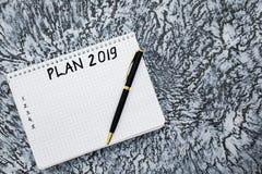 计划在2019年,笔记薄和笔在织地不很细灰色背景 库存图片