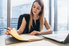 计划她的工作日的确信的女性企业家坐在认为她的书桌的候宰栏看笔记本  库存照片