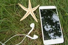 计划您的海滩假日并且旅行在与电话,耳机,海星的草 库存图片