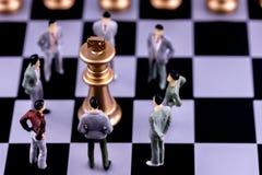 计划成功的商业领袖概念主导的战略  微型人民小形象站立在国王附近的商人 库存图片