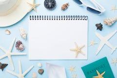 计划暑假、旅游业和假期背景 有辅助部件的旅客笔记本在蓝色桌面看法 平的位置 库存图片