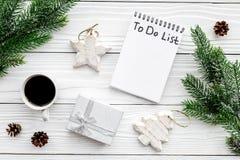 计划的新年 与要做名单的笔记本在圣诞节玩具、云杉的分支和pinecones附近在白色木背景 图库摄影