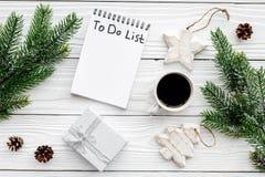计划的新年 与要做名单的笔记本在圣诞节玩具、云杉的分支和pinecones附近在白色木背景 免版税库存图片
