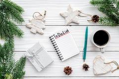 计划的新年 与要做名单的笔记本在圣诞节玩具、云杉的分支和pinecones附近在白色木背景 免版税图库摄影