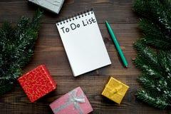 计划的新年 与要做名单的笔记本在礼物盒附近,在木背景顶视图的云杉的分支 免版税库存照片