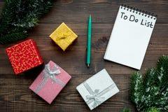计划的新年 与要做名单的笔记本在礼物盒附近,在木背景顶视图的云杉的分支 库存图片