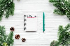 计划的新年 与要做在白色木背景顶视图的名单在云杉的分支附近和pinecones的笔记本 库存图片