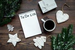 计划的新年 笔记本与要做名单的在圣诞节玩具附近,云杉的分支和pinecones在木背景冠上 库存照片