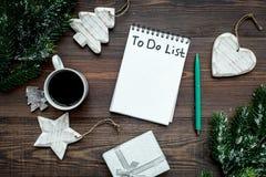 计划的新年 笔记本与要做名单的在圣诞节玩具附近,云杉的分支和pinecones在木背景冠上 库存图片