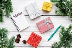计划的新年 笔记本与要做名单的在礼物盒附近,云杉的分支和pinecones在白色木背景冠上 免版税库存照片