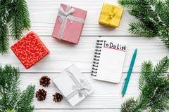 计划的新年 笔记本与要做名单的在礼物盒附近,云杉的分支和pinecones在白色木背景冠上 库存照片