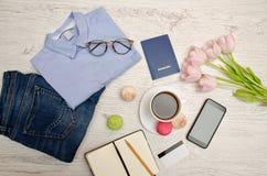 计划行程 蓝色衬衣、牛仔裤、护照、咖啡杯、笔记薄和电话 秀丽蓝色聪慧的概念表面方式构成妇女 顶视图 免版税库存照片
