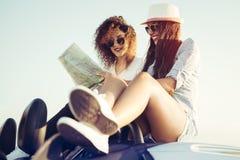 计划他们的与敞篷车的两个女孩夏天海边旅行 库存图片