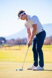 计划他的射击的观点的高尔夫球运动员对别针 图库摄影