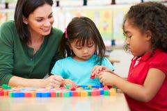 计数与老师的基本的学生在教室 免版税库存照片