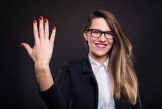 计数五个手指的愉快的年轻女实业家 免版税库存图片