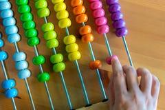 计数五颜六色的小珠算盘的手 免版税库存图片