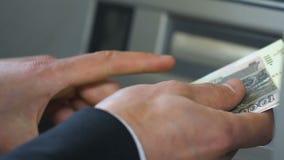 计数俄罗斯卢布的商人的手临近ATM,投入金钱在钱包 股票视频