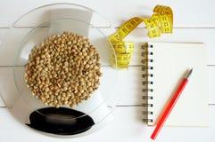 计数卡路里、蛋白质、油脂和碳水化合物在食物 在桌等级的扁豆五谷 免版税库存照片