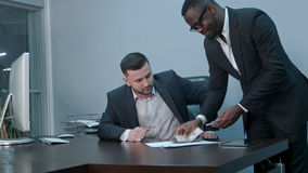 计数在书桌上的金钱和给票据的美国黑人的商人他的白种人伙伴,握手的他们 免版税图库摄影