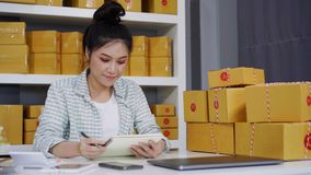 计数在她自己的工作购物的网上事务的年轻女人企业家小包箱子 股票视频