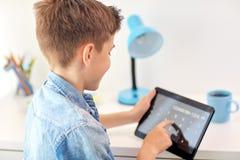 计数在片剂个人计算机计算器的学生男孩 库存照片