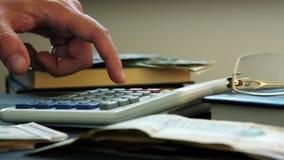 计数在计算器和金钱的手在书桌上 股票录像