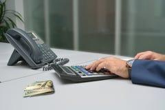 计数在计算器的商人在办公室 免版税库存照片