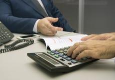 计数在计算器的商人在办公室 图库摄影