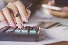 计数在计算器的女商人手月度费用有信用卡和巧妙的电话迷离背景  库存照片