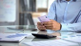 计数欧元和企划公司预算的男性会计在办公室,银行业务 免版税库存照片