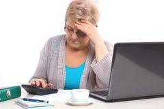 计数电费单的担心的年长资深妇女在她的家,在晚年的金融证券 库存照片