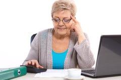 计数电费单的年长资深妇女在她的家,在晚年的金融证券 免版税库存图片