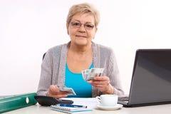 计数电费单的年长资深妇女现金在她的家,在晚年的金融证券 库存图片