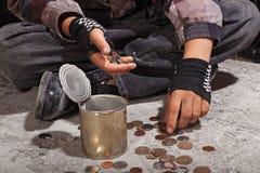 计数硬币的叫化子孩子坐损坏的水泥地板 免版税库存图片