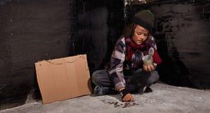 计数硬币的年轻叫化子男孩-坐地面 免版税库存图片