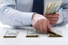 计数美元钞票的银行出纳员 免版税库存图片