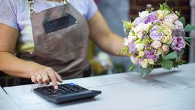 计数花束的费用与计算器的女性卖花人在花店 图库摄影