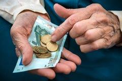 计数货币的高级妇女 免版税库存照片