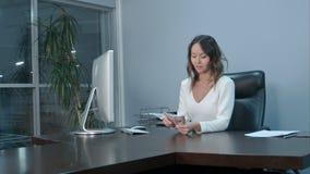 计数金钱的一个年轻亚裔办公室工作者的画象 免版税库存图片