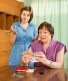 计数金钱的女孩和她的年长母亲 库存照片