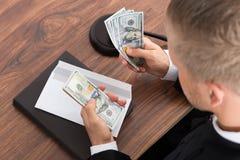 计数金钱的法官在法庭 免版税库存图片