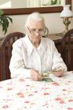 计数金钱的老妇人,当坐在桌上时 免版税库存图片